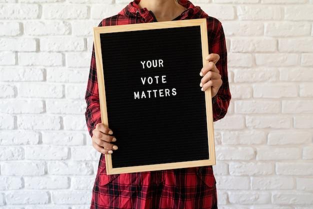Conceito de votação. mulher segurando o quadro de cartas com o texto seu voto é importante em fundo de tijolo branco
