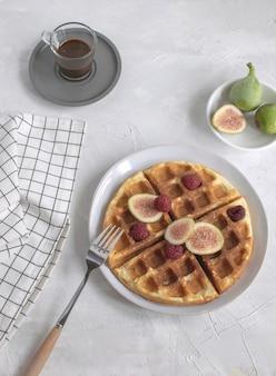 Conceito de waffles belgas figos framboesas café expresso fundo de madeira branco lay plana espaço de cópia
