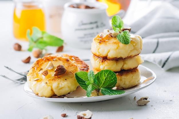 Conceito delicioso do alimento de café da manhã. panquecas de queijo cottage, syrniki, coalhada fritos com mel
