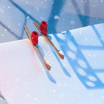 Conceito dental de inverno com escovas e creme dental em forma de esquis com botas de feltro vermelhas, montando a montanha.