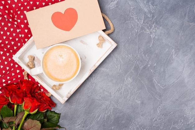 Conceito dia dos namorados. café da manhã, envelope com coração vermelho, rosas na mesa cinza. espaço livre. espaço para texto.