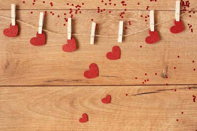 Conceito dia dos namorados. guirlanda de forma de coração. corações de glitter vermelho pendurado na corda em madeira