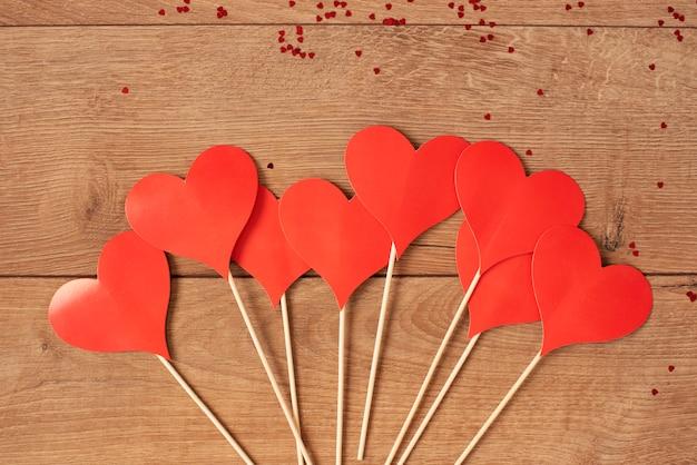Conceito dia dos namorados. muitos corações de papel vermelho em um de madeira