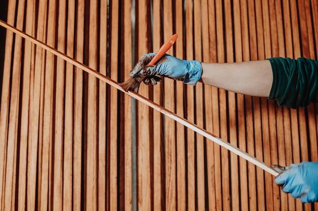 Conceito diy, mulher pintando alguns pedaços de madeira para ela um novo mobiliário doméstico