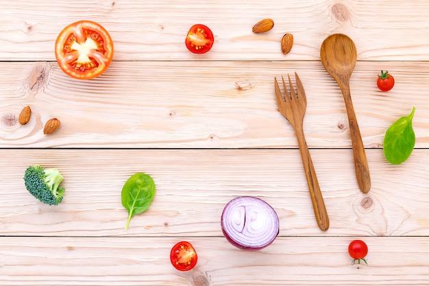 Conceito do alimento e da salada com configuração lisa dos ingredientes crus em de madeira branco.
