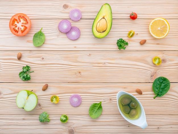 Conceito do alimento e da salada com configuração lisa dos ingredientes crus em de madeira.