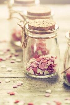 Conceito do amor com os frascos em um fundo de madeira, tonificação pastel.