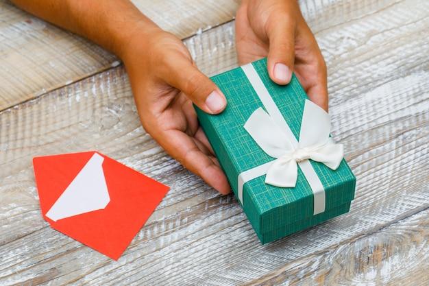 Conceito do aniversário com o cartão no envelope na opinião de ângulo alto do fundo de madeira. homem passando a caixa de presente.
