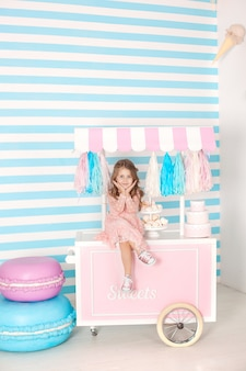 Conceito do aniversário e da felicidade - menina feliz que senta-se em um trole com gelado e doces contra de uma barra de chocolate. bolo multi-colorido grande. quarto decorado para uma aniversariante