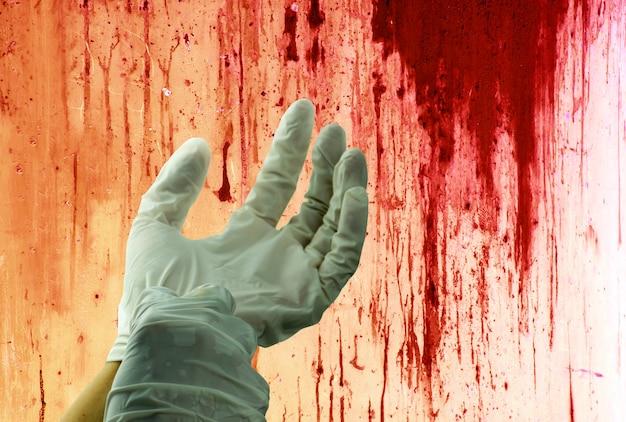 Conceito do assassinato ensanguentado na parede e na mão humana com luvas de borracha.