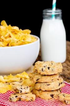 Conceito do café da manhã, cookies e cereais do cornflake com vidro de leite na tabela.