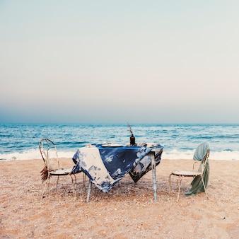 Conceito do céu do feriado da costa de mar da refeição das cadeiras de tabela