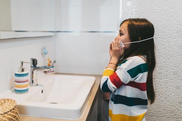 Conceito do coronavirus covid-19. menina com máscara protetora no rosto, lavando as mãos no banheiro com sabonete antibacteriano.