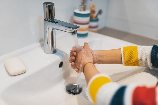 Conceito do coronavirus covid-19. menina lavando as mãos no banheiro com sabonete antibacteriano.