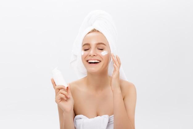 Conceito do cuidado de pele da juventude da beleza - retrato caucasiano bonito da cara da mulher que guarda e que apresenta o produto de creme do tubo.