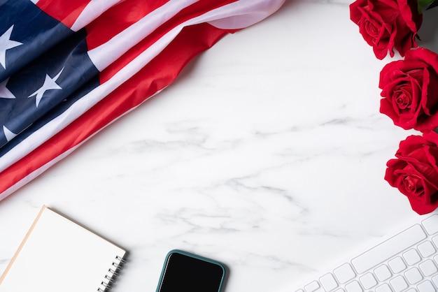 Conceito do dia da independência dos eua, o quarto de julho ou celebração da venda online do dia do memorial. bandeira nacional e rosa vermelha sobre fundo de mesa de mármore.