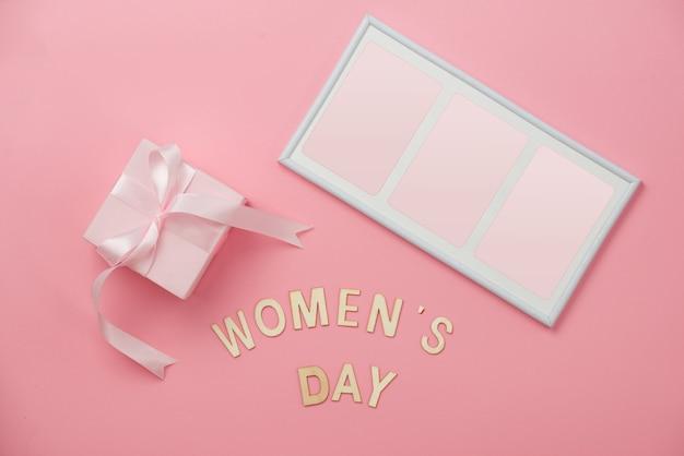 Conceito do dia da mulher, feliz dia da mulher, dia internacional da mulher. texto do dia da mulher, presente de madeira rosa com moldura em fundo coral