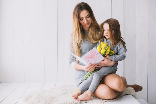 Conceito do dia das mães com mãe e filha segurando o cartão