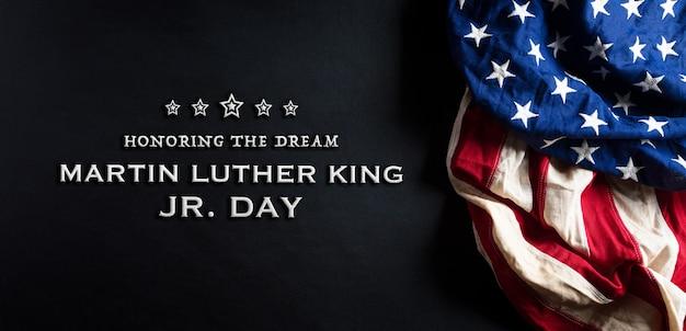 Conceito do dia de martin luther king. bandeira americana contra fundo preto de madeira