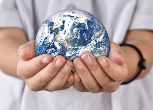 Conceito do dia do meio ambiente, terra nas mãos da criança.