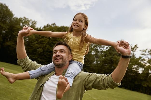 Conceito do dia do pai, menina animada, brincando com o pai no parque, sentado em seus ombros e