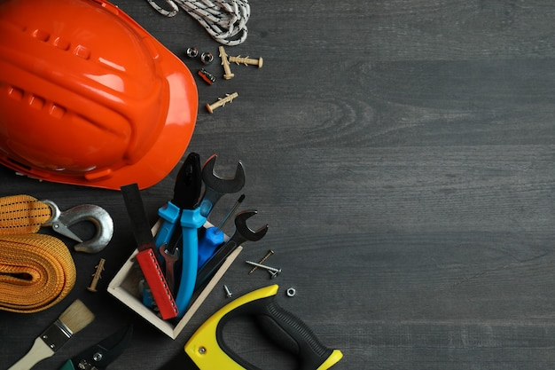 Conceito do dia do trabalho com diferentes ferramentas de construção em fundo escuro de madeira