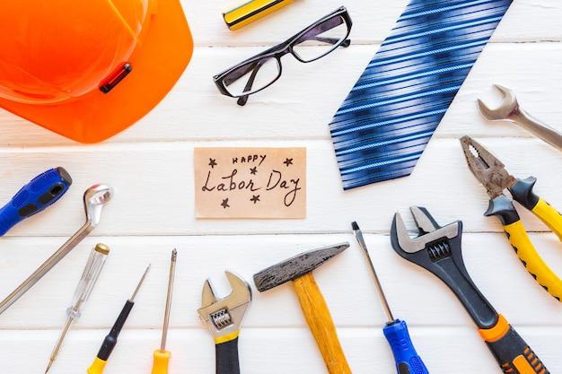 Conceito do dia do trabalho dos eua. diferentes tipos de chaves, ferramentas úteis, etiqueta em fundo branco rústico.