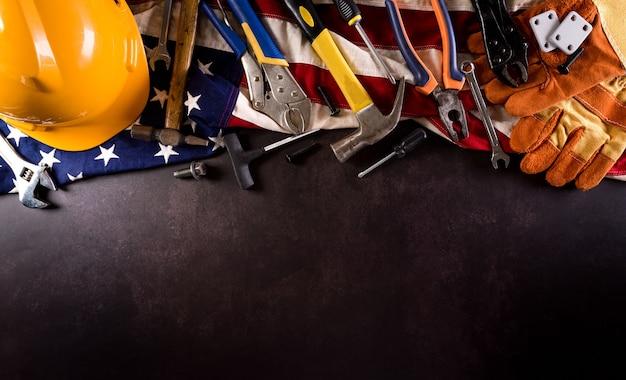 Conceito do dia do trabalho feliz. bandeira americana com diferentes ferramentas de construção em fundo de pedra escura.