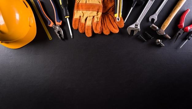 Conceito do dia do trabalho feliz. diferentes ferramentas de construção em fundo escuro de madeira.