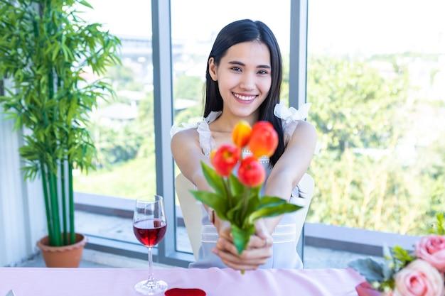 Conceito do dia dos namorados, feliz de sorrir jovem asiática sentada à mesa segurando um vaso de flores falso no fundo do restaurante