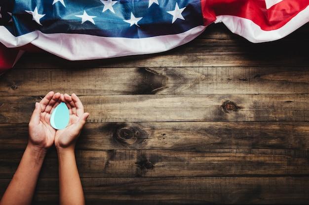 Conceito do dia mundial da água mãos segurando uma gota d'água em um fundo de madeira e a bandeira dos eua