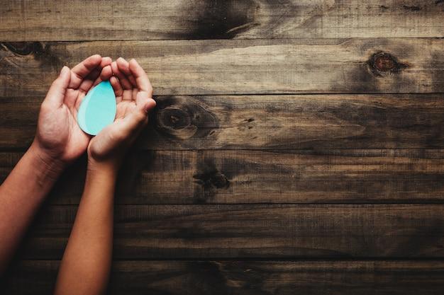 Conceito do dia mundial da água - mãos segurando uma gota d'água