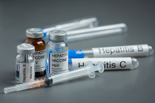 Conceito do dia mundial da hepatite com ferramentas médicas e pílulas colocadas na superfície cinza
