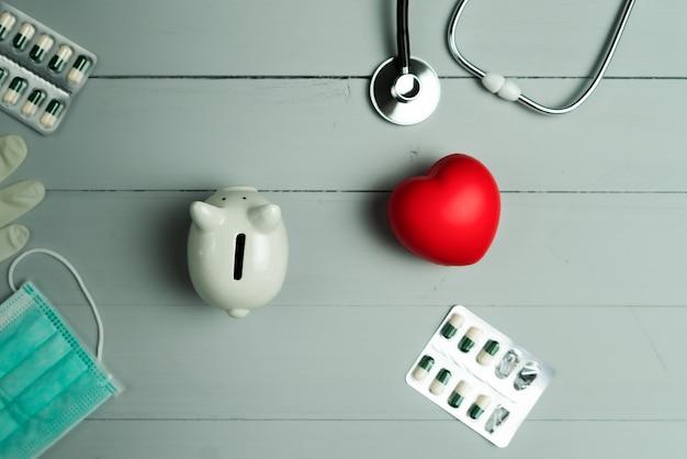 Conceito do dia mundial da saúde e seguro médico de saúde com coração vermelho e instrumento médico em fundo de madeira