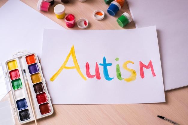 Conceito do dia mundial de conscientização do autismo. coração e mãos de papel sobre fundo azul. transtorno do espectro do autismo (asd).