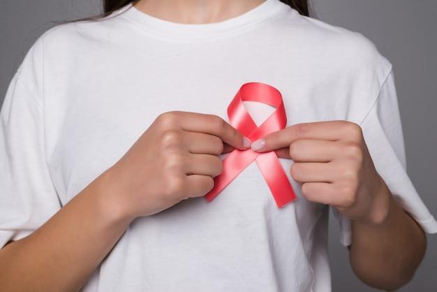 Conceito do dia mundial do câncer de mama, cuidados de saúde - mulher usava camiseta branca com fita rosa para conscientização, aumento simbólico da cor do laço em pessoas que vivem com doenças de tumor de mama em mulheres