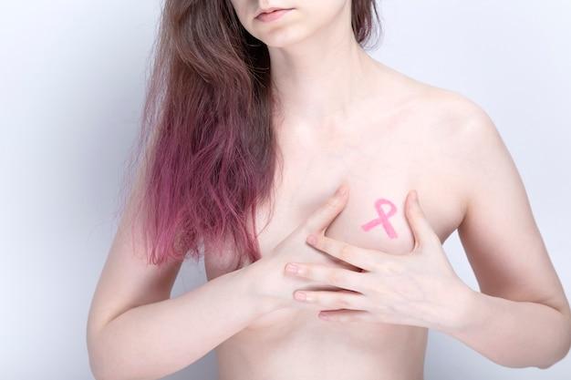 Conceito do dia mundial do câncer de mama. mulher cobre o peito com as mãos com uma fita rosa pintada. outubro, mês de conscientização sobre o câncer de mama.