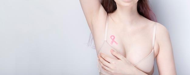 Conceito do dia mundial do câncer de mama. mulher de sutiã com fita rosa pintada no peito. outubro, mês de conscientização sobre o câncer de mama. copie o espaço