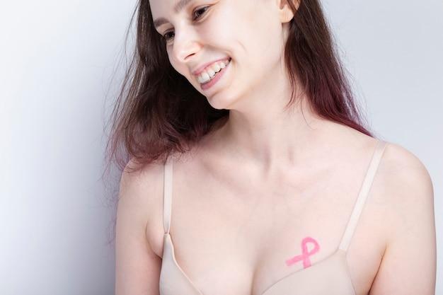 Conceito do dia mundial do câncer de mama. mulher de sutiã com fita rosa pintada no peito. outubro mês de conscientização sobre o câncer de mama