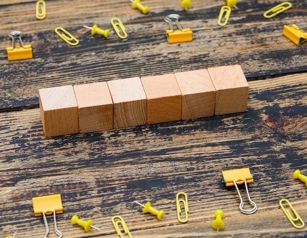 Conceito do escritório com cubos de madeira, clipes de papel, grampos da pasta na opinião de ângulo alto do fundo de madeira.
