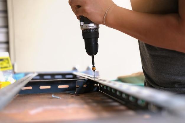 Conceito do faça você mesmo, os artesãos usam furadeiras elétricas para montar peças de ferro antigas. faça uma prateleira no seu fim de semana livre.