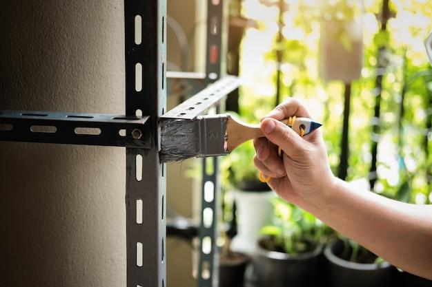Conceito do faça você mesmo, os artesãos usam tinta anti-ferrugem para pintar peças de ferro antigas. faça uma prateleira no seu fim de semana livre.