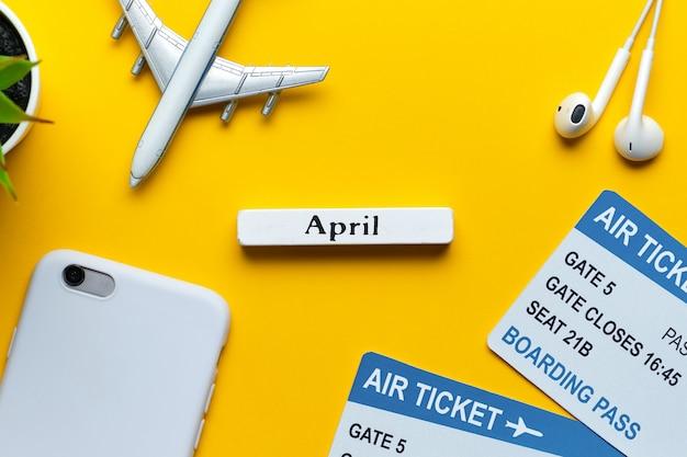 Conceito do feriado de abril com avião e bilhetes em uma opinião superior do fundo amarelo.
