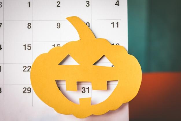 Conceito do feriado de dia das bruxas, papel do corte da abóbora com calendário.