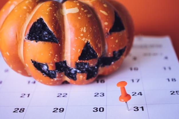 Conceito do feriado de dia das bruxas, pin no planeamento do evento do calendário e abóbora de dia das bruxas.