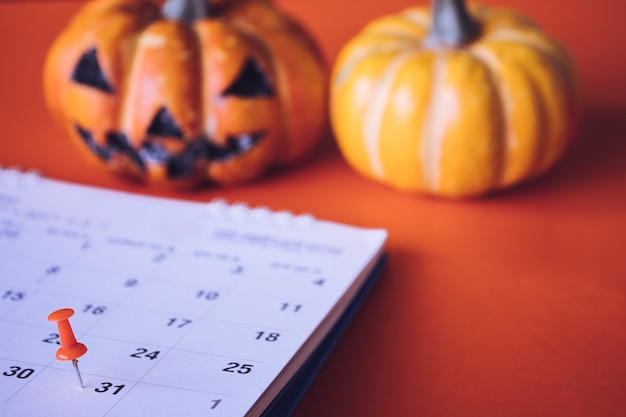 Conceito do feriado de dia das bruxas, pin no planeamento do evento do calendário e abóboras de dia das bruxas.
