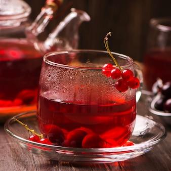 Conceito do inverno ou do outono: chá vermelho quente da baga com corintos vermelhos e cereja na tabela marrom rústica.