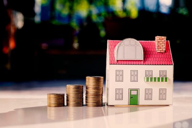 Conceito do investimento de bens imobiliários, moedas do dinheiro que crescem e casa diminuta na mesa.