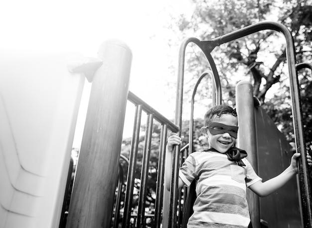 Conceito do menino da criança da liberdade do super-herói da jarda do campo de jogos