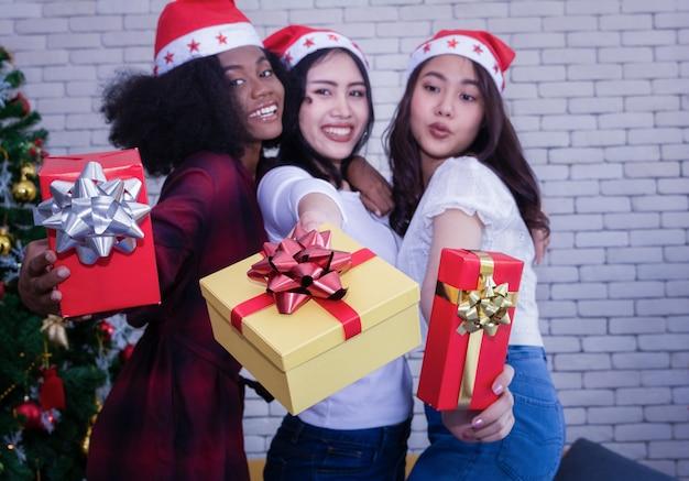 Conceito do natal e da felicidade - menina arenosa de sorriso que guarda muitas caixas de presente.